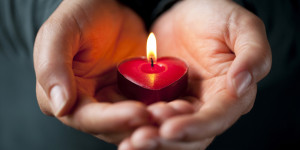 Heart-shaped candle in her hands